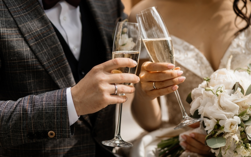 Front view of wedding couple's hands with champagne glasses and